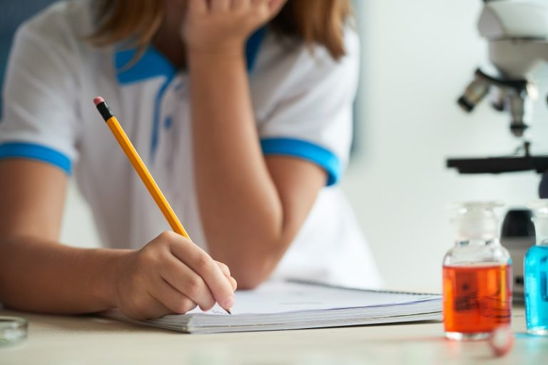 Cropped image of schoolgirl writing in texbook at chemistry class